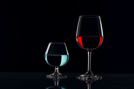 Crystal glasses with black bottom and red and blue drinks Banque d'images