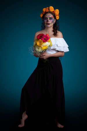 Latin woman with Catrina makeup, black dress and a bouquet of flowers in her hands