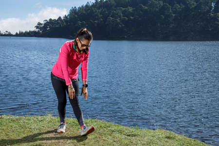 Athlete stretching after running on the shore of a lake, sitting on a stone surrounded by trees