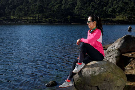 Athlete resting on the shore of a lake sitting on a stone, after running in the forest.