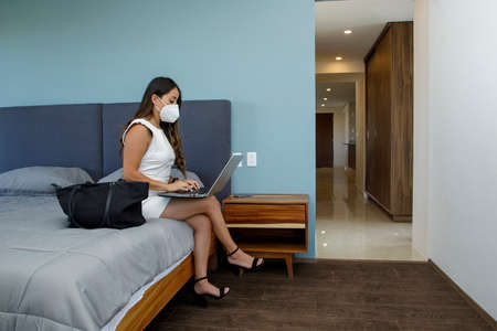 Young Latina businesswoman wearing a mask while working on her laptop, in her apartment bedroom doing home office. Foto de archivo