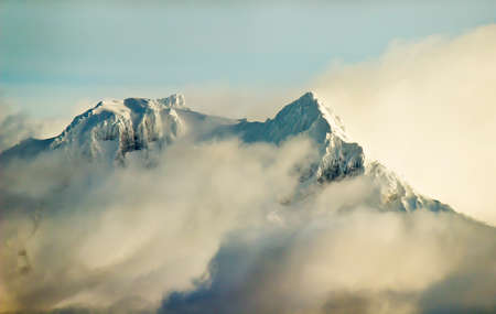 mountaintop: Snowy Mountain Peak Covered in Clouds