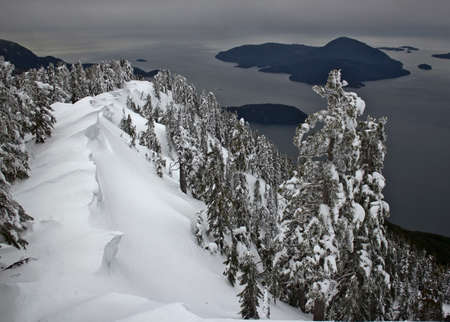 View from the top of the mountain at a beautiful snowy ridge and ocean in the background