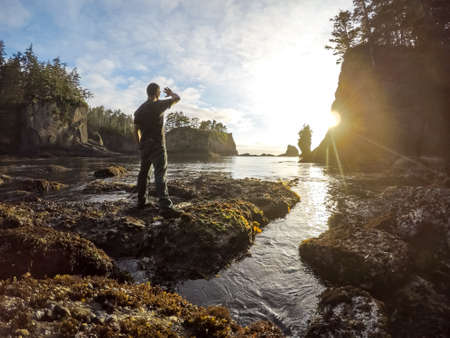 flattery: Explorer watching the bright sunset in Cape Flattery, on the Washington Coast
