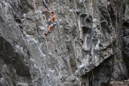 Rock Climber climbing a steep cliff on a mountain. Taken near Squamish, British Columbia, Canada
