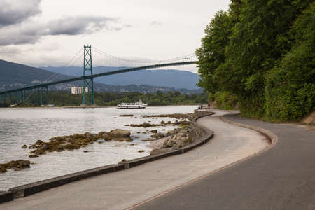 Lions Gate Bridge in Stanley Park on the Seawall. Taken in Downtown Vancouver, British Columbia, Canada, on a cloudy evening. 版權商用圖片