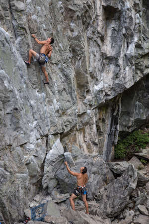 rock bottom: Rock Climber climbing a steep cliff on a mountain., while his partner is belaying him at the bottom. Taken near Squamish, British Columbia, Canada