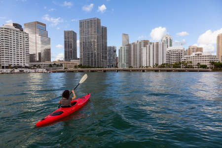 Adventurous girl kayaking in front of a modern Downtown Cityscape during a sunny evening. Taken in Miami, Florida, United States of America. Reklamní fotografie