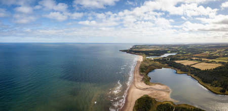 Aerial panoramic view of a beautiful sandy beach on the Atlantic Ocean. Taken in Cavendish, Prince Edward Island, Canada.
