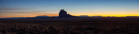 Dramatic panoramic landscape view of a dry desert with a mountain peak in the background during a vibrant sunset. Taken at Shiprock, New Mexico, United States. 版權商用圖片