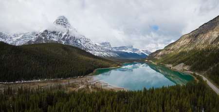 Aerial panoramic landscape view of a glacier lake surrounded by Canadian Rocky Mountains during a cloudy day. Taken in Banff, Alberta, Canada.