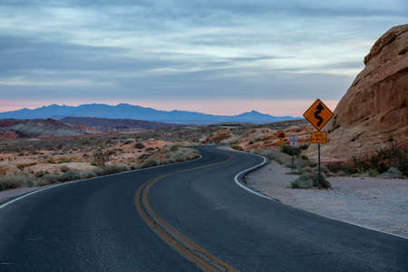 Winding road sign on a scenic road in the desert during a cloudy sunrise. Taken in Valley of Fire State Park, Nevada, United States.