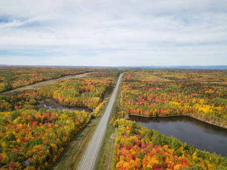 Aerial view of highway in a beautiful Canadian Landscape during fall color season. Taken near Belledune, New Brunswick, Canada.