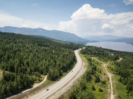 Aerial view of Trans-Canada Highway during a vibrant sunny summer day. Taken near Shuswap Lake, Blind Bay, BC, Canada.