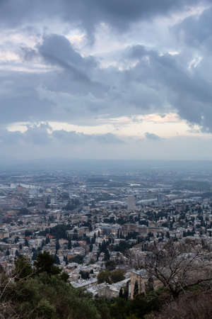 Beautiful view of a city on the coast of Mediterranean Sea during a cloudy sunset. Taken in Haifa, Israel.