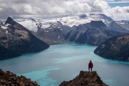 Woman standing on top of the Mountain overlooking a beautiful glacier lake. Taken on Panorama Ridge, Garibaldi, Near Whister, BC, Canada.