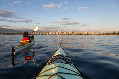 Girl Sea Kayaking in front of Downtown City during a vibrant sunny summer sunset. Taken in Vancouver, BC, Canada. Stok Fotoğraf