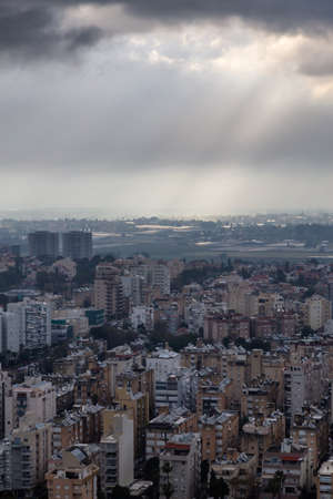 Aerial view of a residential neighborhood in a city during a cloudy sunrise. Taken in Netanya, Center District, Israel. 免版税图像