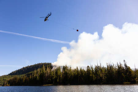Helicopter fighting BC forest fires during a hot sunny summer day. Taken near Port Alice, Northern Vancouver Island, British Columbia, Canada. 版權商用圖片