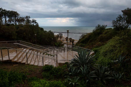Stairs going down to the sandy beach during a cloudy sunrise. Taken in Netanya, Center District, Israel.