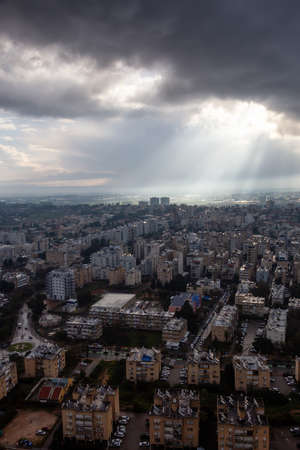 Aerial view of a residential neighborhood in a city during a cloudy sunrise. Taken in Netanya, Center District, Israel.