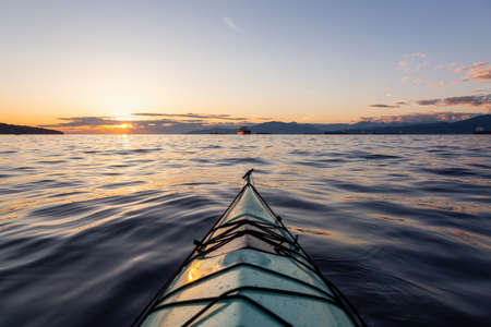Sea Kayaking during a vibrant sunny summer sunset. Taken in Vancouver, BC, Canada. Stock Photo