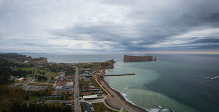 Aerial panoramic view of a beautiful modern town on the Atlantic Ocean Coast during a cloudy sunset. Taken in Percé, Quebec, Canada. Фото со стока