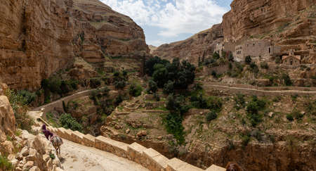 Beautiful view of Monastery of St. George in a rocky canyon during a sunny day. Located near Jerusalem in Wadi Qelt, Israel. Stock Photo