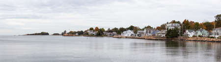 Panoramic view on residential homes on the Rocky Coast during a cloudy morning. Taken on the Atlantic Ocean in New Haven, Connecticut, United States.