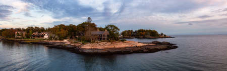 Panoramic seascape view of beautiful homes on a rocky Atlantic Coast during a vibrant sunset. Taken in New Haven, Connecticut, United States.