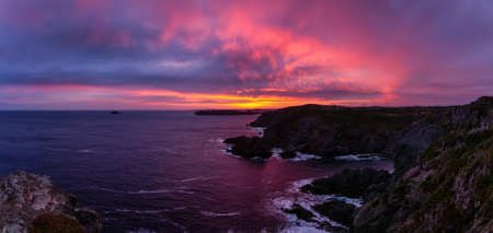 Striking panoramic seascape view on a rocky Atlantic Ocean Coast during a colorful sunrise. Taken at Crow Head, North Twillingate Island, Newfoundland and Labrador, Canada. Imagens