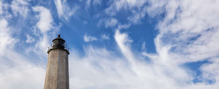 Panoramic view on a lighthouse on the Atlantic Ocean Coast during a cloudy morning. Taken in Lighthouse Point Park, New Haven, Connecticut, United States. Stock Photo