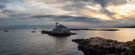 Panoramic seascape view of a beautiful home on a rocky island during a vibrant sunset. Taken on the Atlantic Ocean in New Haven, Connecticut, United States. Stock Photo