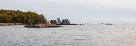Panoramic view on residential homes on the Rocky Coast during a cloudy day. Taken on the Atlantic Ocean in New Haven, Connecticut, United States. Stock Photo