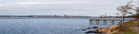 Panoramic view of a wooden quay on the Atlantic Ocean Coast during a cloudy morning. Taken in Lighthouse Point Park, New Haven, Connecticut, United States. Stock Photo
