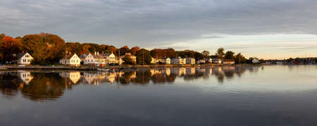 Panoramic view of residential homes by the Mystic River during a vibrant sunrise. Taken in Mystic, Stonington, Connecticut, United States.