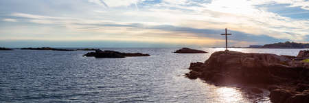 Panoramic seascape view of a cross on a rocky shore during a vibrant sunset. Taken on the Atlantic Ocean in New Haven, Connecticut, United States.