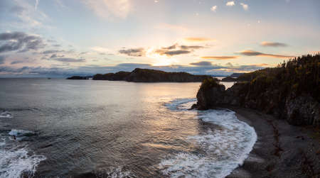 Striking panoramic landscape view of a rocky Atlantic Ocean Coast during a vibrant sunrise. Taken at Beachside, Newfoundland and Labrador, Canada. Imagens