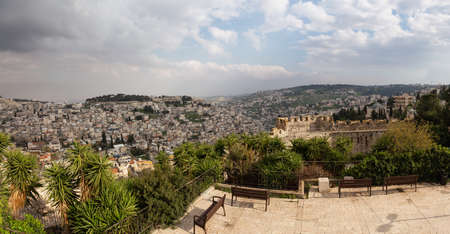 Beautiful panoramic view of the Walls of Jerusalem surrounding the Old City with the cityscape in the background during a cloudy day. Taken near the Jerusalem, Israel.