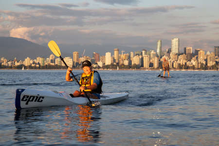 Vancouver, BC, Canada - August 30, 2018: People racing on Paddle Boards and Surf Ski during a vibrant summer sunset.