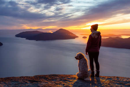 Adventurous Girl Hiking on top of a Mountain with a dog during a colorful sunset. Taken on Tunnel Bluffs Hike, near Vancouver and Squamish, British Columbia, Canada. 版權商用圖片