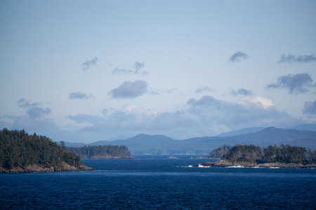 Northern Vancouver Island, British Columbia, Canada. Rocky Islands on the Pacific Ocean during a sunny and cloudy day with Islands and the Mainland in the background. 版權商用圖片
