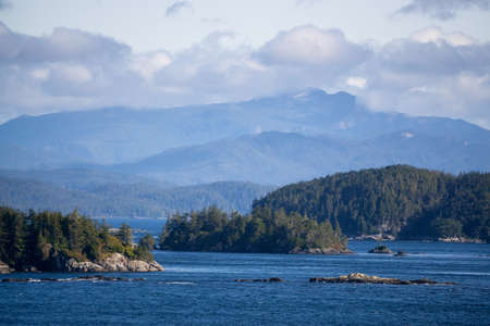 Northern Vancouver Island, British Columbia, Canada. Rocky Islands on the Pacific Ocean during a sunny and cloudy day with Islands and the Mainland in the background.