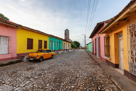 View of an Old Classic Taxi Car in the streets of a small Cuban Town with Church in the Background during a vibrant sunny sunrise. Trinidad, Cuba.
