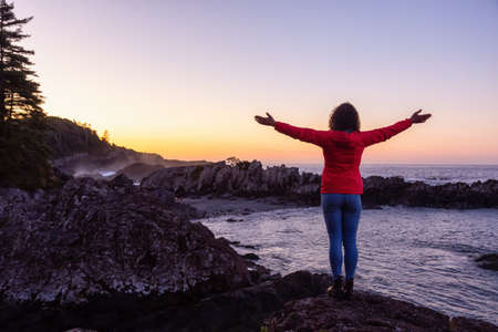Adventurous Girl Enjoyin the Beautiful View of the Rocky Ocean Coast during a colorful and vibrant morning sunrise. Taken in Ucluelet, near Tofino, Vancouver Island, BC, Canada.
