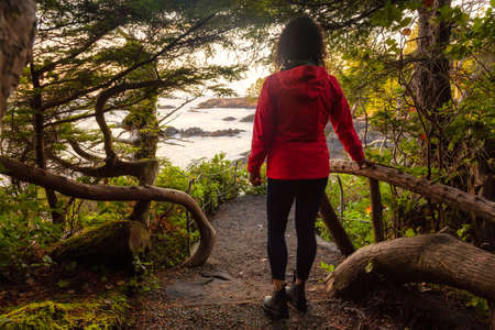 Adventurous Girl walking in a Forest with a beautiful view on the Ocean Coast during a vibrant colorful sunrise. Wild Pacifc Trail, Ucluelet, Vancouver Island, BC, Canada. 版權商用圖片