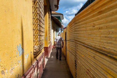 Narrow Pathway in an old city near a construction site and residential homes. Taken in Trinidad, Cuba.