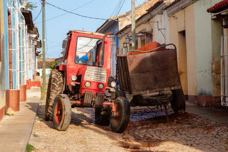Trinidad, Cuba - June 12, 2019: Male Worker on a Tractor is working in a small Cuban Town during a vibrant sunny day. 新聞圖片
