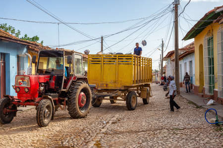 Trinidad, Cuba - June 12, 2019: Men Workers picking up garbage on a Tractor is working in a small Cuban Town during a vibrant sunny day. 版權商用圖片 - 143141005