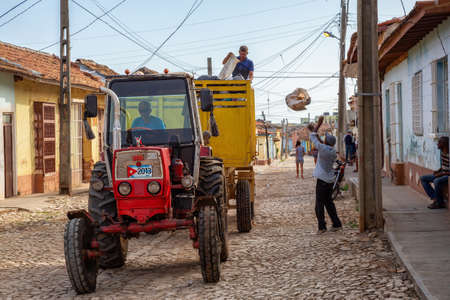 Trinidad, Cuba - June 12, 2019: Men Workers picking up garbage on a Tractor is working in a small Cuban Town during a vibrant sunny day.